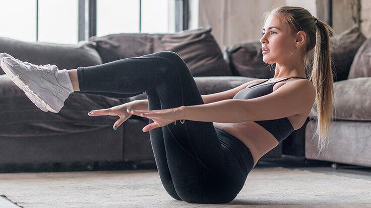Eine junge Frau macht in ihrer Wohnung Sport und stärkt dabei ihre Muskeln und ihre Gesundheit