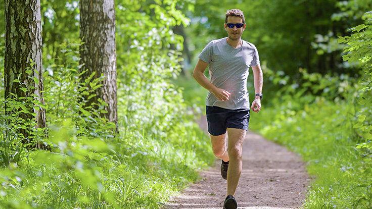 Mann beim Trailrunning im Wald