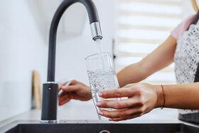 Eine Frau füllt sich Leitungswasser aus dem Hahn in ein Glas ein