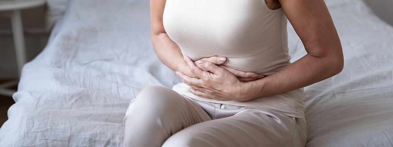 Eine junge Frau hat Magenschmerzen.