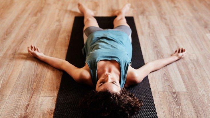 Frau liegt für Progressive Muskelentspannung auf einer Matte.
