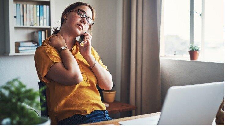 Eine Frau telefoniert an ihrem Arbeitstisch und massiert dabei erschöpft ihren Nacken