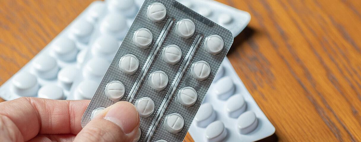 Eine Person hält Tabletten in der Hand.