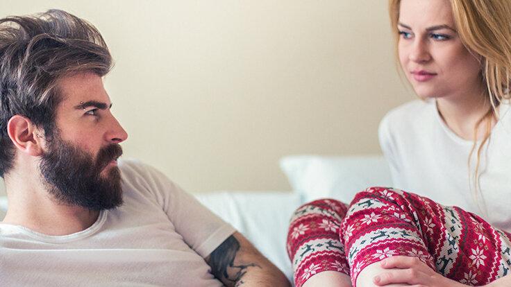 Ein Mann und eine Frau sitzen im Bett und schauen sich an. Sie sprechen über Verhütung und Geschlechtskrankheiten.