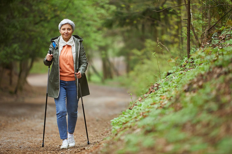 Ältere Frau beim Walken im Wald und das trotz einer Kniearthrose.