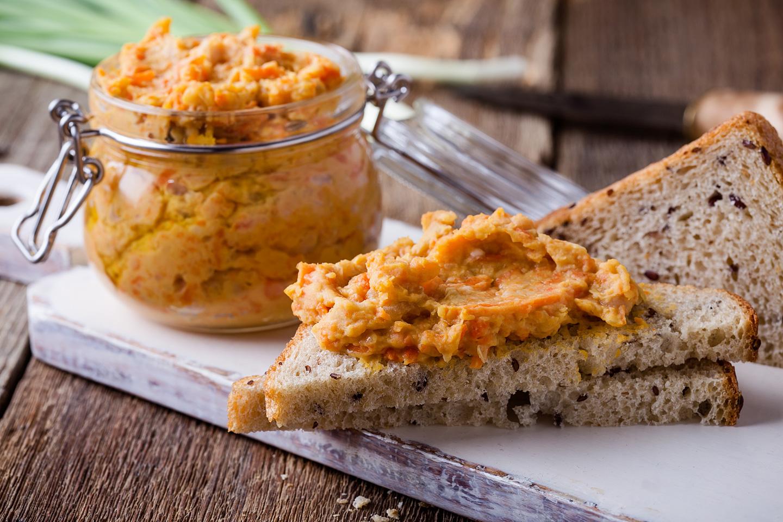 Karottenaufstrich in einem Glas und auf Brot geschmiert.