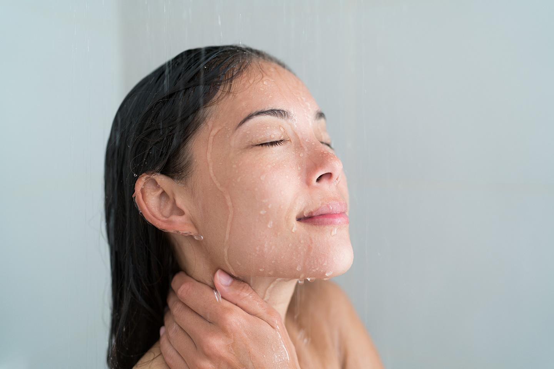 Eine junge Frau lässt unter der Dusche Wasser über ihr Gesicht laufen.