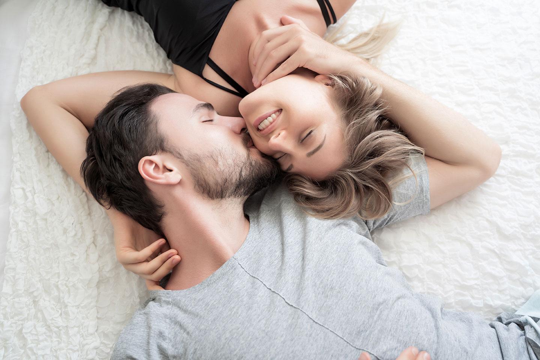 Ein Paar liegt glücklich im Bett.