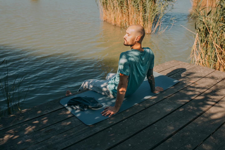 Ein Mann führt auf seiner Yogamatte am Wasser eine Achtsamkeitsübung zur Krebsbewältigung durch.