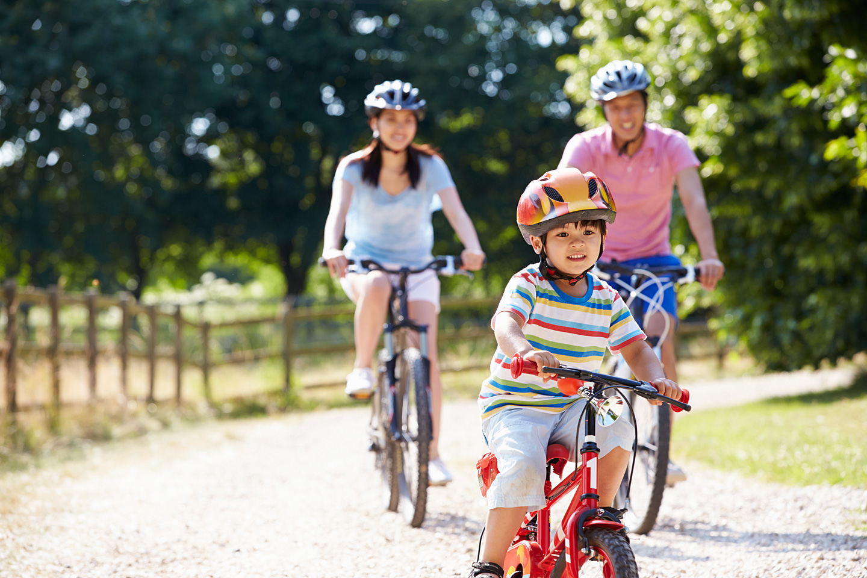 Eine Familie mit einem kleinen Sohn ist mit dem Rad unterwegs.