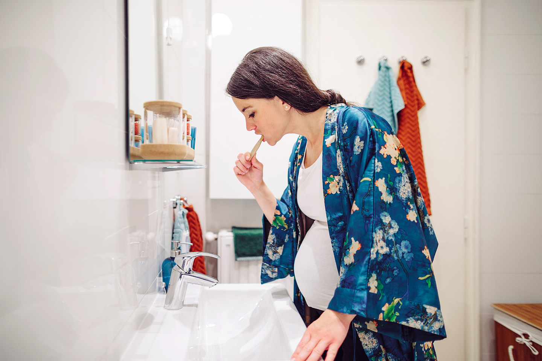 Eine junge Frau putzt sich die Zähne, denn in der Schwangerschaft spielt die Zahnreinigung eine wichtige Rolle.
