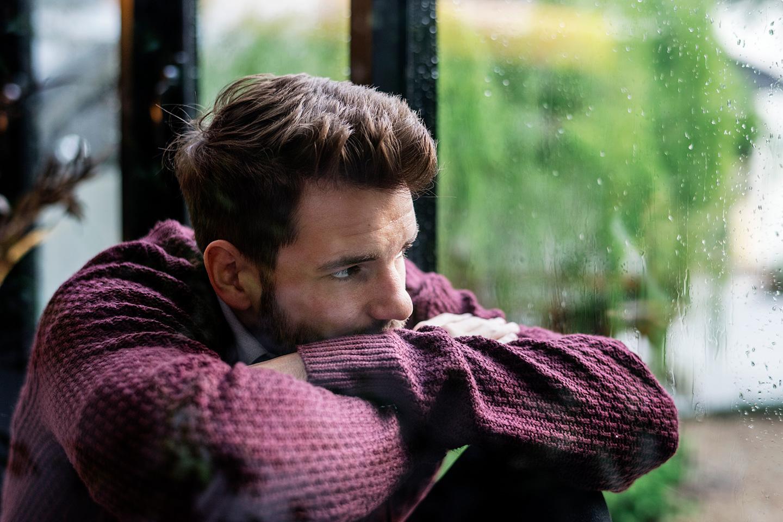 Ein Mann ist traurig und nachdenklich und schaut aus dem Fenster.