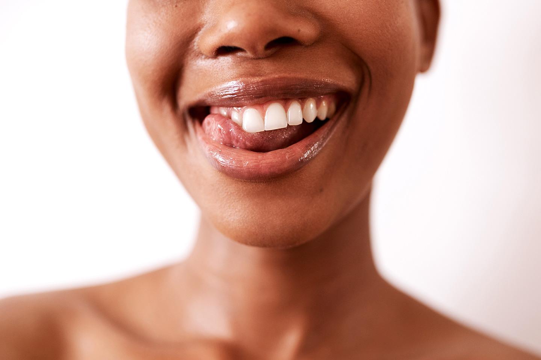 Eine junge Frau streicht mit der Zunge über ihre Zähne.